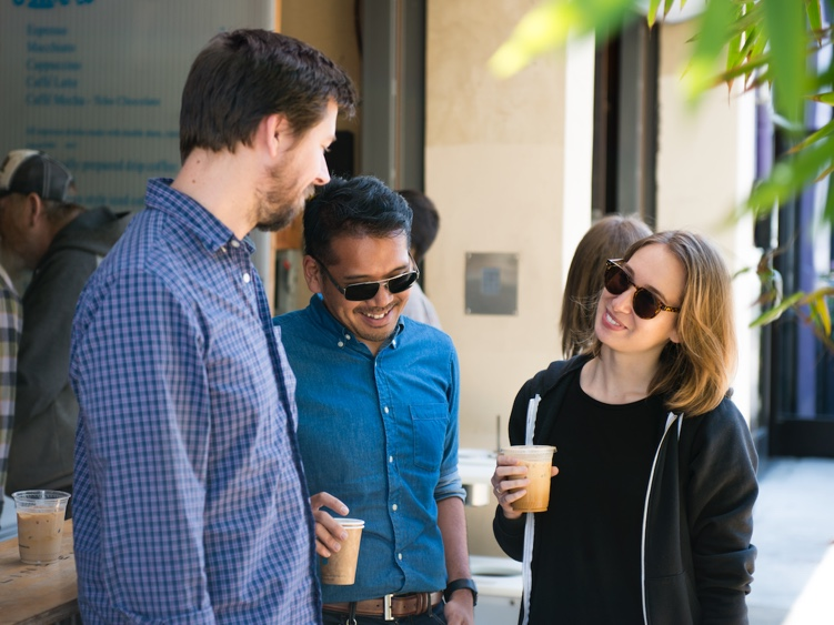 Three people standing together outside with coffees in their hands.